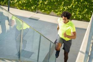 hombre negro corriendo arriba al aire libre. hombre joven haciendo ejercicio. foto