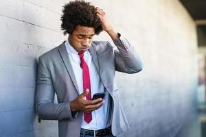 Worried Black Businessman using his smartphone outdoors. photo