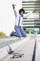 empresario negro saltando sobre una patineta cerca de un edificio de oficinas. foto