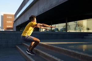 hombre negro haciendo sentadillas con saltar en un escalón. foto