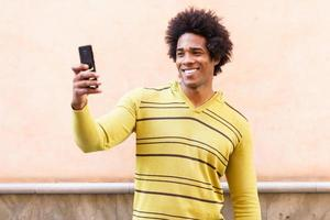 Black man with afro hair and headphones using smartphone. photo