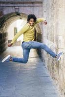hombre negro con cabello afro saltando de alegría foto