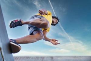 vista desde abajo del hombre negro saltando sobre su carrera. foto