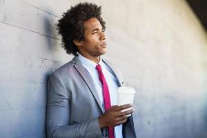 Black Businessman taking a coffee break with a take-away glass photo