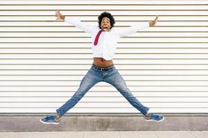 hombre de negocios negro saltando al aire libre. hombre con pelo afro. foto