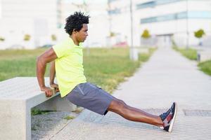 Hombre negro haciendo ejercicio de inmersión de tríceps en un banco de la calle de la ciudad. foto