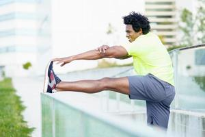 Hombre negro con cabello afro haciendo estiramientos después de correr al aire libre. foto