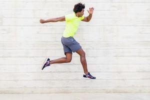 entrenamiento de hombre negro corriendo saltos para fortalecer sus piernas. foto