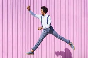 hombre negro tomando una selfie con su teléfono inteligente mientras salta al aire libre. foto