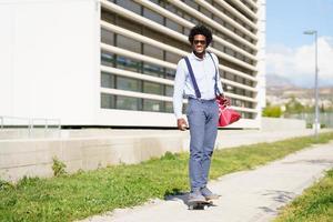 Black businessman riding skateboard near office building. photo