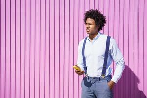 Black man with afro hairstyle using smartphone photo
