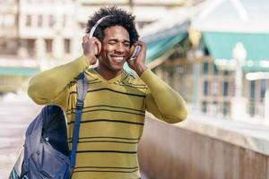 Black man listening to music with wireless headphones photo