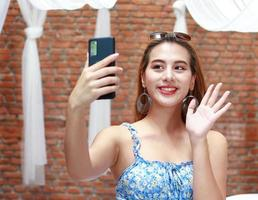 Asian woman happily take selfies at home on vacation photo