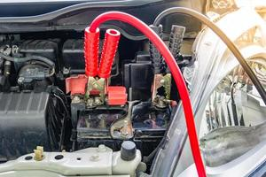 Carga de la batería del coche con cables de puente a través de la electricidad. foto