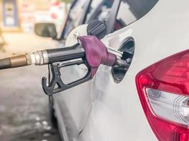 Fuel nozzle to add fuel in car at petrol station. photo