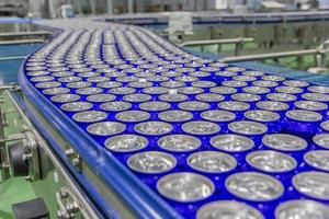 Packed cans on the conveyor belt in berverage factory photo