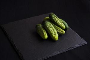 Natural fresh green cucumbers from a home garden on a black background photo