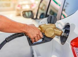 Hand refilling the car with fuel photo
