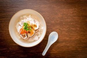 Boiled rice soup with seafood photo