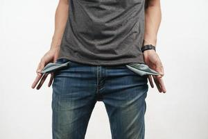 Man turning out the jean pocket to showing empty pocket. no money. photo