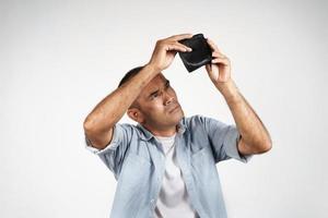 hombre maduro molesto sosteniendo y mirando dentro de su billetera vacía. foto