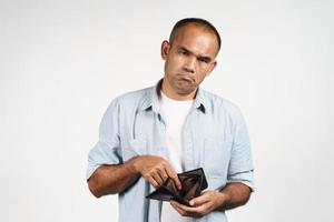 Upset man holding and looking inside his empty wallet. no money. photo