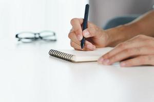 Cerca de las manos del hombre escribiendo en el bloc de notas, cuaderno con lápiz. foto