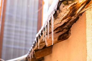 Roof covered with snow, icicles on roof isolated close up. photo