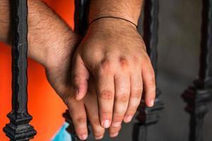 Prisoner man holding hands on jail bars. Hands on prison bars. photo
