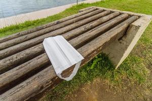 Protective mask discarded over a public bench photo
