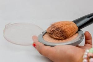 maquillaje, polvos compactos con brocha foto