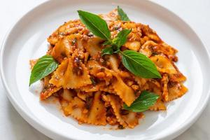 Farfalle pasta with basil and garlic in tomato sauce photo