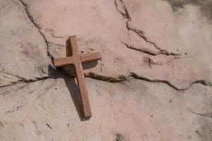 Christian wooden cross on the ground. photo