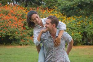novia cabalga detrás de novio. pareja relajante en el jardín foto