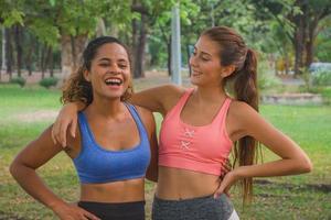 mujeres jóvenes sanas que se relajan después de los ejercicios en el parque. foto