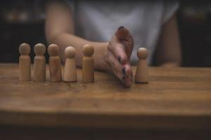 simple wooden figures are being separated by a hand photo