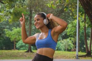African american  woman listening to music with headphones and smiling in park. photo