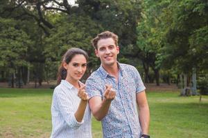 Hermosa joven pareja feliz haciendo forma de corazón con la mano al aire libre foto