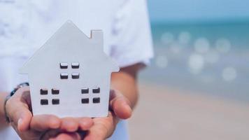 mano que sostiene el modelo de casa de madera en la playa. foto