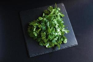 Fresh dill and parsley on a black board photo