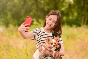 Una niña hace un selfie en un teléfono inteligente con perros en la naturaleza. foto