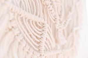 Wall panel in boho style made of cotton threads of natural color photo