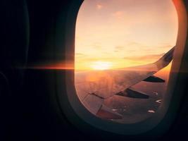 en vuelo de avión vista desde la ventana con un impresionante fondo de puesta de sol foto