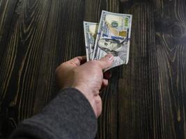 Hand with money on a wooden background photo