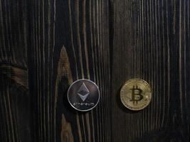 Bitcoin and Ethereum on a wooden background photo