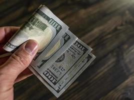 male hand holds two banknotes of hundred dollars photo
