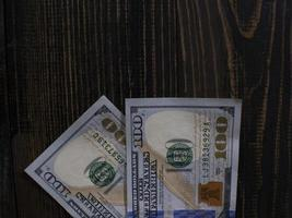 Two hundred dollars bills on a wooden background photo
