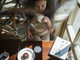 attractive girl with curly hair sits in a cafe drinks coffee photo