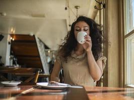 attractive girl sits in a cafe at the table and drinks coffee photo