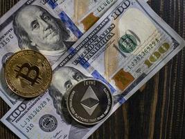 Bitcoin and Ethereum on banknotes of hundred dollars on a wooden photo